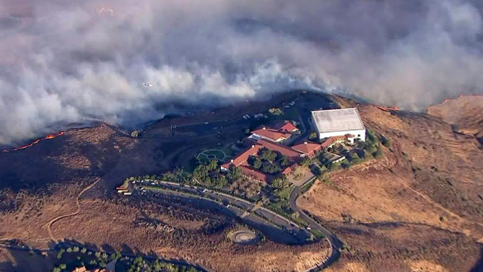 This photo from video provided by KTLA-TV shows the Ronald Reagan Presidential Library as flames from the Easy fire approach in Simi Valley, Calif., Wednesday, Oct. 30, 2019. The new wildfire erupted in wind-whipped Southern California, forcing the evacuation of the Library and nearby homes, as both ends of the state struggled with blazes, dangerously gusty weather and deliberate blackouts. Library spokeswoman Melissa Giller said the hilltop museum was safe. She said hundreds of goats are brought in each year to eat away vegetation that could fuel wildfires on the 300-acre (120-hectare) grounds, where Reagan and his wife, Nancy, are buried next to each other on a hillside. (KTLA-TV via AP)
