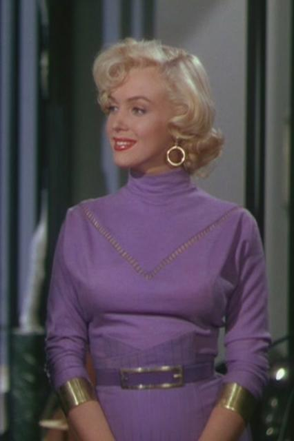 """<em><h2>Gentlemen Prefer Blondes (1953)</h2></em><br>The white dress on the subway grate from <em>The Seven Year Itch</em> gets more ink — as does the iconic pink dress from this film's closing musical number """"Diamonds Are A Girl's Best Friend."""" But, for me, Marilyn's most stunning fashion moment is her purple sweater (with daring V-shaped cutout), her matching purple wiggle skirt that could only have been sewn on, and her shiny, gold cuffs. This look only gets more impressive when Marilyn's character, Lorelei, accessorizes it with (spoiler alert!) a stolen diamond tiara. <span class=""""copyright"""">Photo: Courtesy of 20th Century Fox.</span>"""