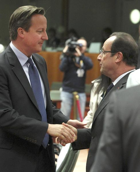 French President Francois Hollande, right, speaks with British Prime Minister David Cameron during a round table meeting at an EU summit in Brussels on Thursday, June 27, 2013. European Union leaders meet in Brussels ostensibly to agree on ways to find more jobs for the young, who've been disproportionately punished by years of crisis and recession. (AP Photo/Yves Logghe)