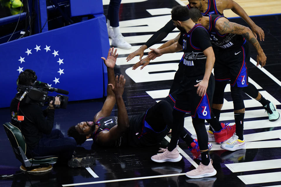 Philadelphia 76ers' Joel Embiid (21) reacts after being fouled on a shot as his teammates reach to help during the first half of Game 2 in a first-round NBA basketball playoff series against the Washington Wizards, Wednesday, May 26, 2021, in Philadelphia. (AP Photo/Matt Slocum)
