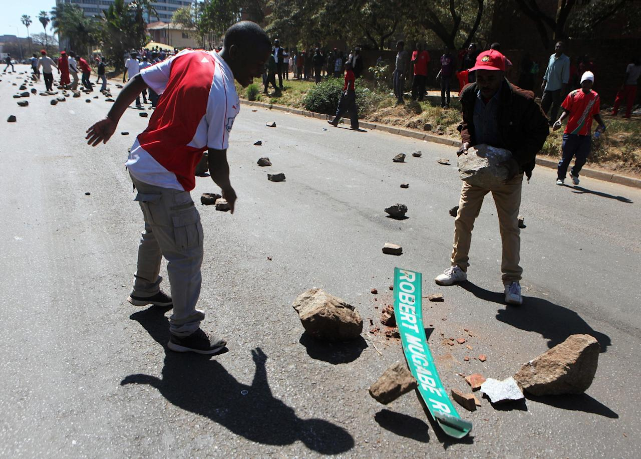 Zimbabwean opposition supporters throw rocks at a street sign bearing the name of President Robert Mugabe during clashes with police in Harare, Zimbabwe, August 26,2016. REUTERS/Philimon Bulawayo     TPX IMAGES OF THE DAY
