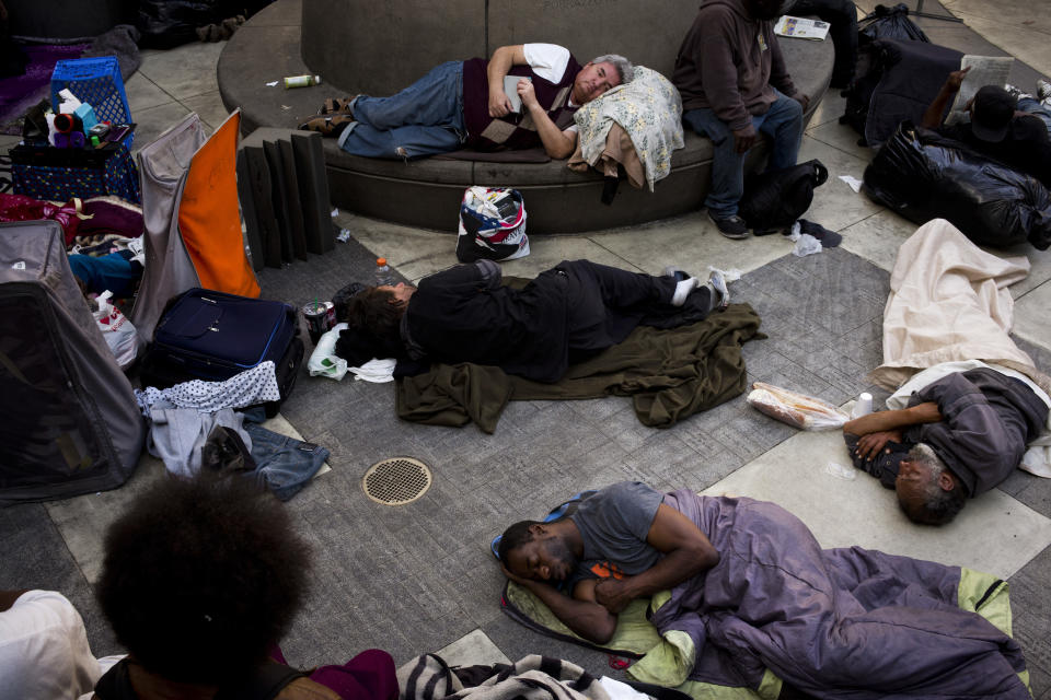 A group of homeless people sleep in the courtyard of the Midnight Mission in Los Angeles. Experts say high rent in America impacts certain cities differently. (AP Photo/Jae C. Hong)