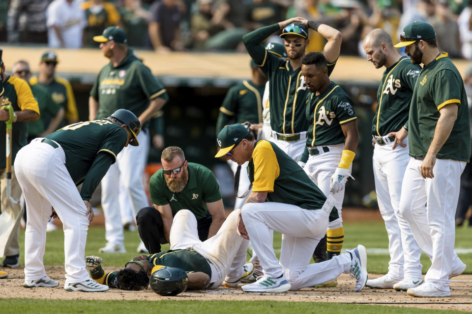 Oakland Athletics manager Bob Melvin, center right, and others attend to Elvis Andrus, center, after he collapsed with an injury after scoring a walk-off win against the Houston Astros in the ninth inning of a baseball game in Oakland, Calif., Saturday, Sept. 25, 2021. The Athletics won 2-1. (AP Photo/John Hefti)