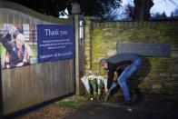 People leave flowers after the announcement of the death of Britain's centenarian fundraiser Captain Sir Tom Moore, in Marston Moretaine near Milton Keynes
