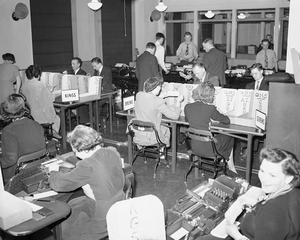 Tabulators record the Associated Press election returns in the offices of IBM in New York City on Election Day, Nov. 3, 1942. The returns are received on the teletype machines (background) and recorded with the aid of the numeric punching and printing machines in the foreground. (AP Photo/Matty Zimmerman)