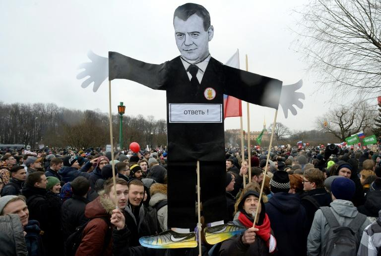 Opposition supporters with a cutout figure depicting Prime Minister Dmitry Medvedev participate in an anti-corruption rally in central Saint Petersburg on March 26, 2017