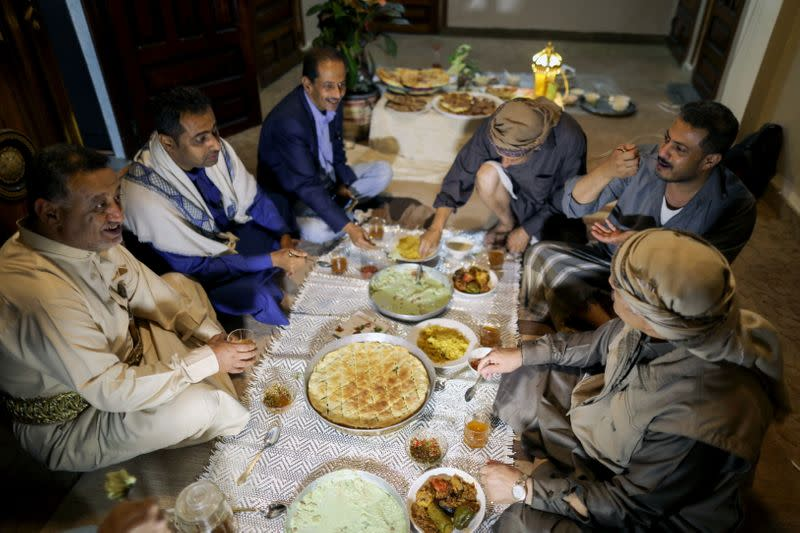 Yemeni singer, Fouad al-Kebsi and his brother Akram, sit with guests for the iftar meal at their family house during the holy month of Ramadan in Sanaa