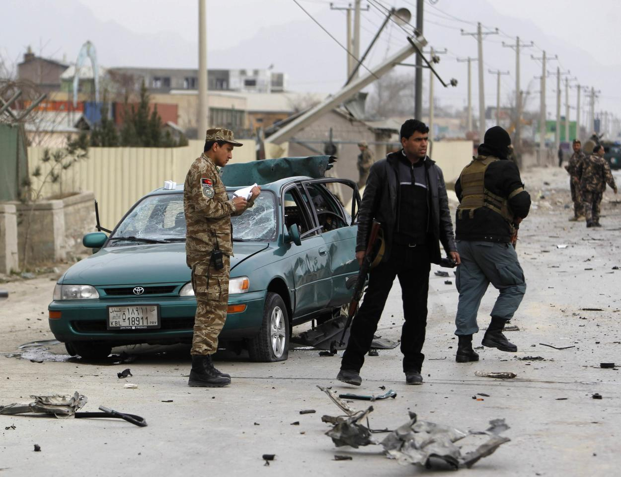 Afghan security personnel inspect a civilian's car at the site of a bomb attack in Kabul December 27, 2013. A suspected suicide bomber attacked a foreign military convoy on the eastern outskirts of the Afghan capital, Kabul, on Friday, killing at least three foreign soldiers, police and the NATO-led International Security Assistance Force (ISAF) said. REUTERS/Omar Sobhani (AFGHANISTAN - Tags: CIVIL UNREST MILITARY CRIME LAW)