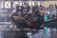 American Magic returns to dock with a hole in the port side of its hull after capsizing on Sunday
