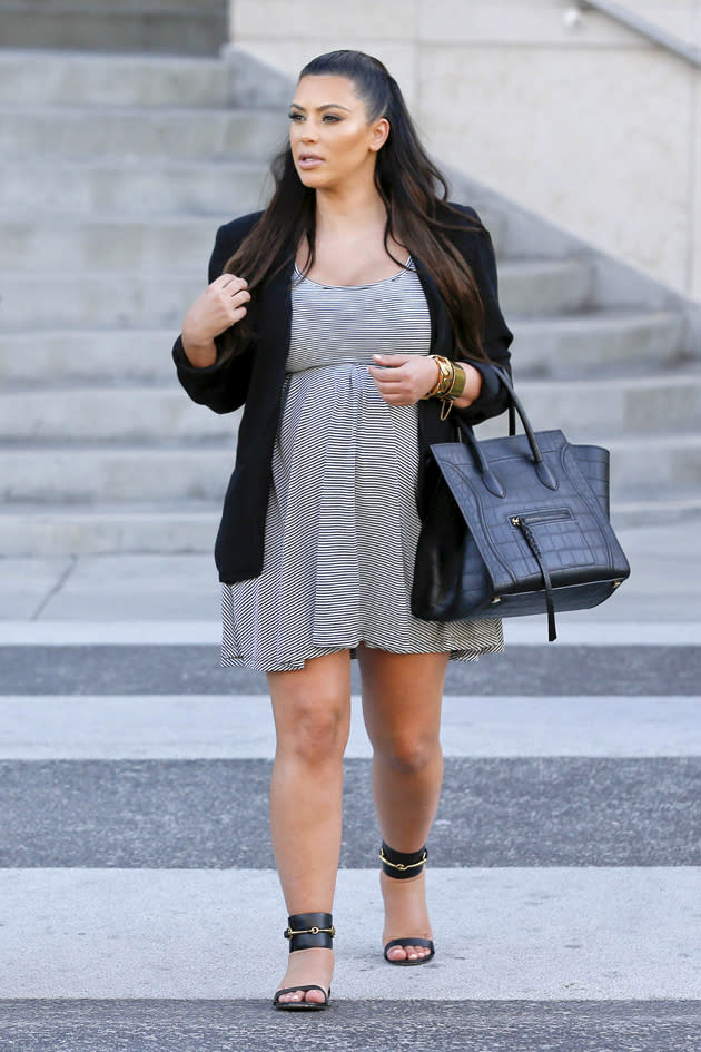 Kim Kardashian ditches the heels and wears flat sandals, and a grey dress which conceals her bump. Copyright [Splash]