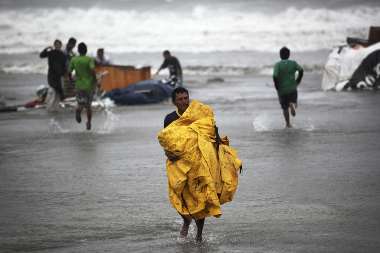 A vendor recovers a plastic tarp after vendors were caught unprepared when high waves dragged their beach stalls into the sea in Veracruz, Mexico, Thursday, Aug. 9, 2012. Tropical Storm Ernesto headed into Mexico's southern Gulf coast as authorities in the flood-prone region prepared shelters, army troops and rescue personnel for drenching rains. (AP Photo/Felix Marquez)