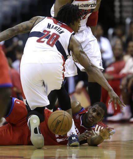 Washington Wizards power forward Cartier Martin, left, defends against Philadelphia 76ers small forward Thaddeus Young who passes the ball after falling to the floor during the first half of an NBA basketball game on Friday, April 12, 2013, in Washington. (AP Photo/Evan Vucci)