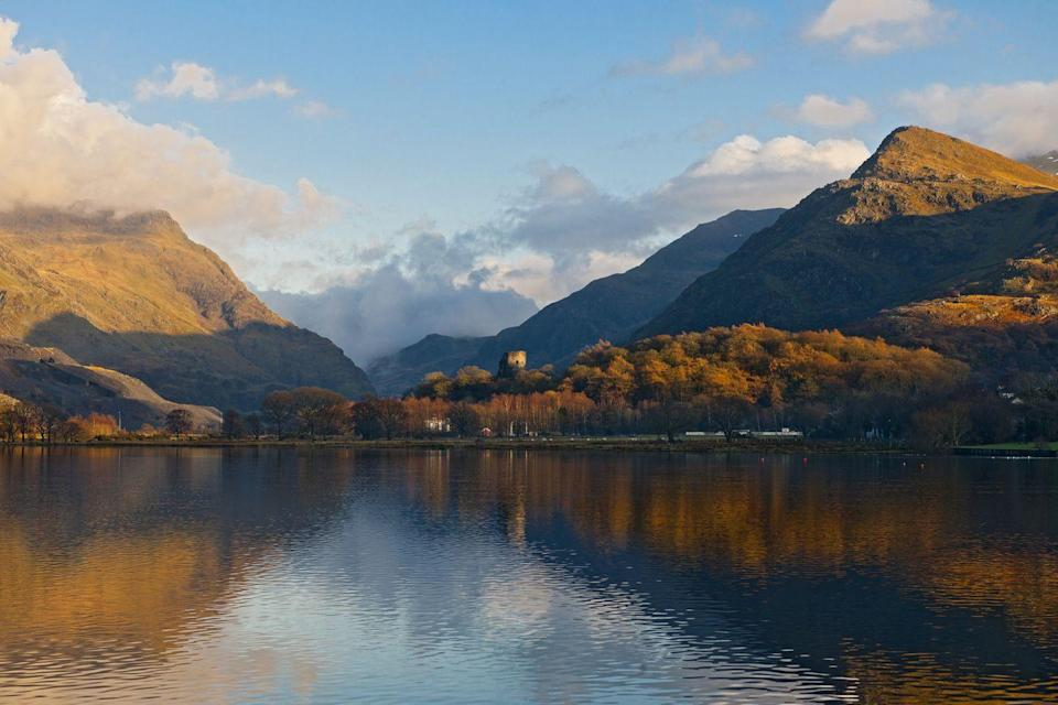 """<p>Have you ever been here before? If you're looking for one of the best places to soak up the autumn colours, then Lake Llyn Padarn is the place to come. Pack your walking boots and make a day of it. </p><p><a class=""""link rapid-noclick-resp"""" href=""""https://www.snowdonia.gov.wales/home"""" rel=""""nofollow noopener"""" target=""""_blank"""" data-ylk=""""slk:MORE INFO"""">MORE INFO</a></p>"""
