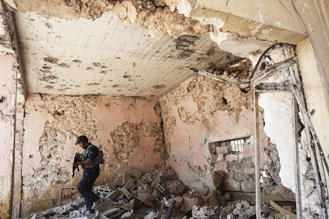 <p>A member of the Iraqi forces patrols inside a damaged building during the advance towards the Old City of Mosul on June 19, 2017 as the ongoing offensive continues to retake the last district still held by the Islamic State (IS) group fighters. (Photo: Ahmad al-Rubaye/AFP/Getty Images) </p>