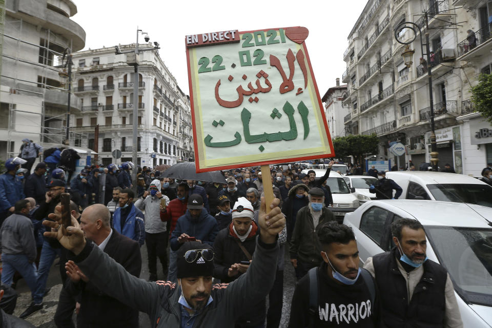 "Algerians demonstrate, one with a poster reading ""Resistance Monday"" in Algiers as they mark the second anniversary of the Hirak movement, Monday Feb. 22, 2021. February 22 marks the second anniversary of Hirak, the popular movement that led to the fall of Algerian President Abdelaziz Bouteflika. (AP Photo/Anis Belghoul)"