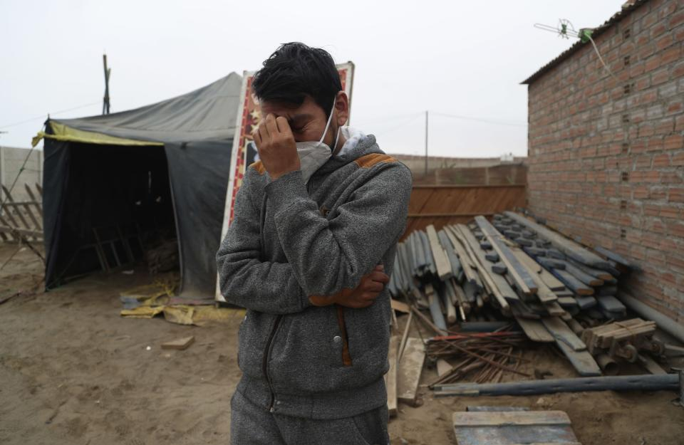"""Circus clown Julio Cesar Chiroque, 38, whose clown name is """"Galleta,"""" or Cookie, tears up as he explains his family's dire economic situation brought by the economic shutdown to curb the spread of COVID-19 outside his home in a poor neighborhood on the outskirts of Lima, Peru, Monday, Aug. 10, 2020. Chiroque's family used to run their own small circus, but since March when the lockdown to curb COVID-19 closed their business, and the requirement for seniors over 60 to self-quarantine kept his father home-bound, they started selling circus food like caramelized apples to survive. (AP Photo/Martin Mejia)"""