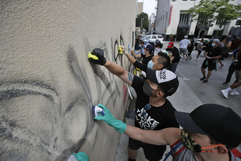 Volunteers clean graffiti from a store wall Monday, June 1, 2020, in Santa Monica, Calif., a day after unrest and protests over the death of George Floyd, a black man who died in police custody in Minneapolis. Floyd died after being restrained by Minneapolis police officers on May 25. (AP Photo/Marcio Jose Sanchez)