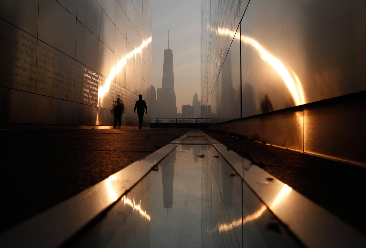A man walks through the 9/11 Empty Sky memorial at sunrise across from New York's Lower Manhattan and One World Trade Center in Liberty State Park in Jersey City, New Jersey, September 11, 2013. Americans will commemorate the 12th anniversary of the September 11 attacks with solemn ceremonies and pledges to not forget the nearly 3,000 killed when hijacked jetliners crashed into the World Trade Center, the Pentagon, and a Pennsylvania field. REUTERS/Gary Hershorn (UNITED STATES - Tags: CITYSCAPE DISASTER ANNIVERSARY TPX IMAGES OF THE DAY)