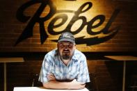 Stephen Chilton, owner of the Rebel Lounge, sits in his music club Thursday, Aug. 26, 2021, in Phoenix. Chilton has struggled to keep his business open in the months since COVID hit Arizona. Arizona on Friday, Aug. 27, surpassed the milestone of 1 million confirmed coronavirus cases after the state reported new infections amid continued wrangling over vaccinations and mask requirements. (AP Photo/Ross D. Franklin)