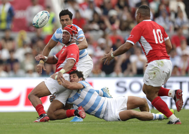 Tonga's Siale Piutau passes the ball to teammate James Faiva, right, as he is tackled by Argentina's Toms Cubelli during the Rugby World Cup Pool C game at Hanazono Rugby Stadium between Tonga and Argentina in Osaka, Japan, Saturday, Sept. 28, 2019. (AP Photo/Aaron Favila)