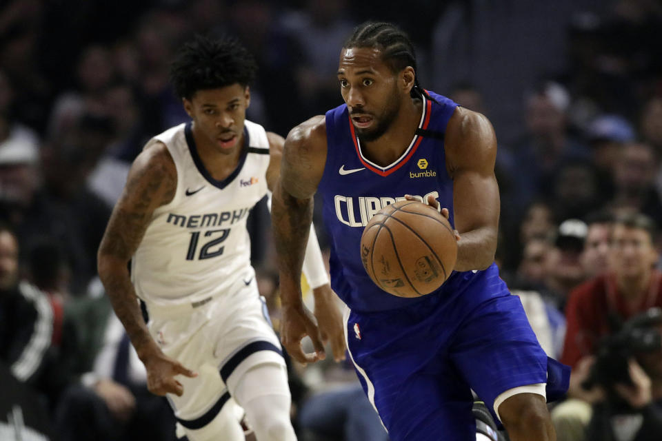 Los Angeles Clippers' Kawhi Leonard, right, dribbles past Memphis Grizzlies' Ja Morant (12) during the first half of an NBA basketball game Saturday, Jan. 4, 2020, in Los Angeles. (AP Photo/Marcio Jose Sanchez)