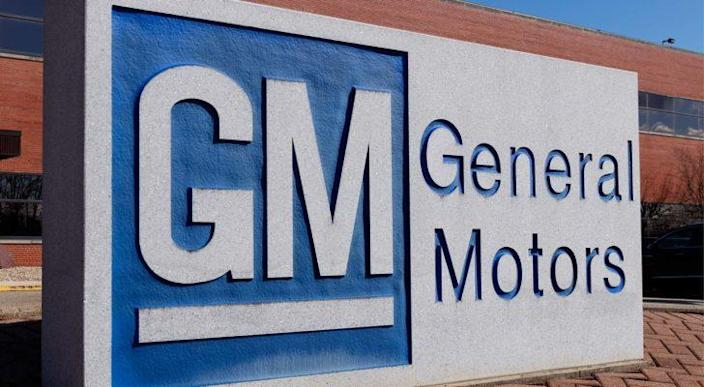 General Motors (GM) sign with blue and white logo and brick building in background