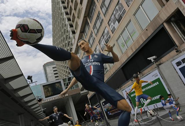 Giant size figures of Swedish striker Zlatan Ibrahimovic, left, and Brazilian striker Neymar, right, are displayed outside a shopping mall in Hong Kong, Thursday, June 12, 2014, to promote the upcoming 2014 World Cup in Brazil. A total of seven 3.5 meters to 4 meters (11 feet 6 inch to 13 feet one inch) tall figures of famous players attract many soccer fans. (AP Photo/Vincent Yu)