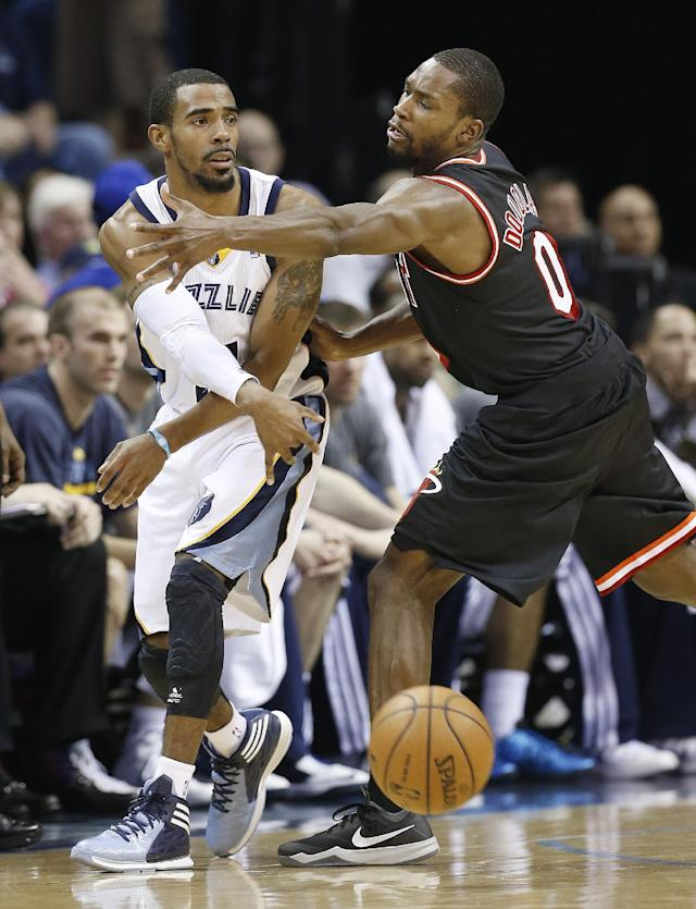 Memphis Grizzlies guard Mike Conley, left, passes around Miami Heat guard Toney Douglas (0) in the first half of an NBA basketball game Wednesday, April 9, 2014, in Memphis, Tenn. (AP Photo/Mark Humphrey)