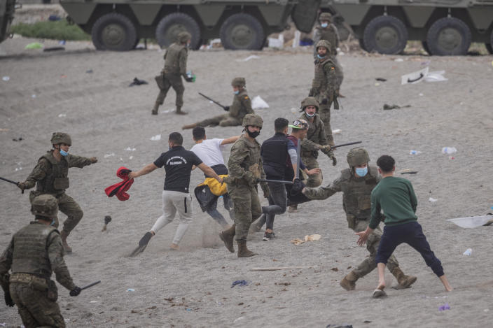 Spanish Army soldiers clash with migrants near the border of Morocco and Spain, at the Spanish enclave of Ceuta, on Tuesday, May 18, 2021. (AP Photo/Bernat Armangue)