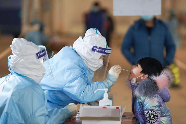 """A medical worker collects a swab sample from a child at a COVID-19 testing site in Daxing District of Beijing, capital of China, Jan. 20, 2021.<span class=""""copyright"""">Xinhua/Ju Huanzong via Getty Images</span>"""