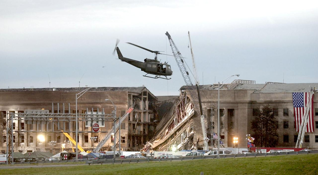 ARLINGTON, VA - SEPTEMBER 14, 2001:  A military helicopter flies in front of the Pentagon at the impact site where a hijacked airliner crashed into the building September 14, 2001 in Arlington, Virginia. This September 11 marks ten years since members of Al Qaeda hijacked four planes, attacking the World Trade Center and the Pentagon and crashing one in Shanksville, Pennsylvania, killing nearly 3,000 people in all. The effects continue to resonate across the global political landscape, as the United States concluded a nearly decade-long search for Al Qaeda leader Osama bin Laden, killing him in May 2011, and struggles to wind down two wars in Afghanistan and Iraq.  (Photo by Stephen J. Boitano/Getty Images)