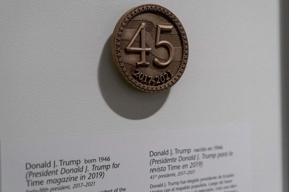 A bronze-looking emblem with the number 45 is visible next to the photo of Trump.