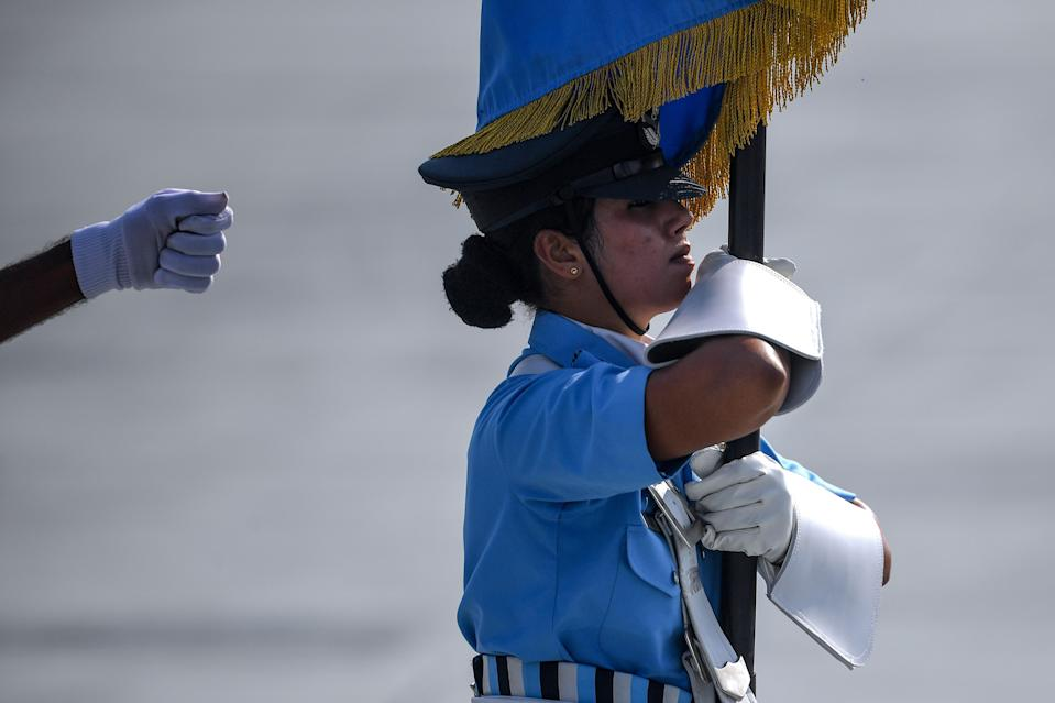 An Indian Air Force (IAF) soldier holds the Indian Air Force flag as she marches during the 88th Air Force Day parade at Hindon Air Force station in Ghaziabad on October 8, 2020. (Photo by Money SHARMA / AFP) (Photo by MONEY SHARMA/AFP via Getty Images)