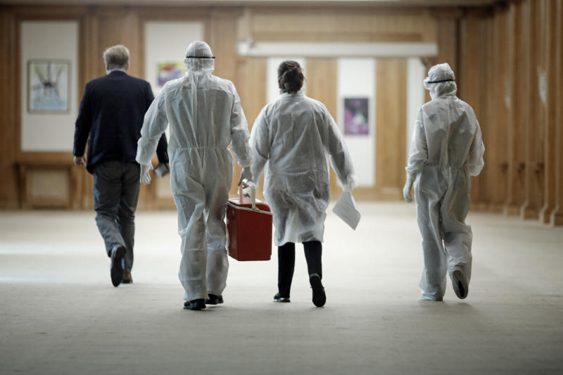 Health officials walk after taking samples for a coronavirus test from journalists and lawmakers in Bucharest, Romania, Friday, March 13, 2020 after it was confirmed that a senator who attended several meetings in the building tested positive for the infection. The caretaker prime minister of Romania, Ludovic Orban, said in a press conference at the parliament, the government, including all ministers, as well as the leadership of the ruling National Liberal Party and all its senators, are going into quarantine after one of the governing party's senators, who took part in high-level meetings, who confirmed to be infected with the coronavirus. (AP Photo/George Calin)