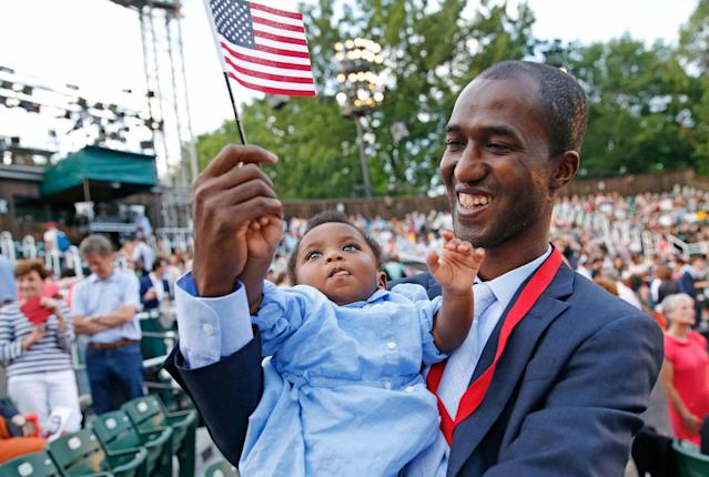 <p>Alpha Saliou Diallo, an refugee from Guinea, holds his daughter Aisha after he became a U.S citizen during a special naturalization ceremony commemorating World Refugee Day at the Delacorte Theater in Central Park, Monday, June 20, 2016, in New York. (Photo: Kathy Willens/AP) </p>