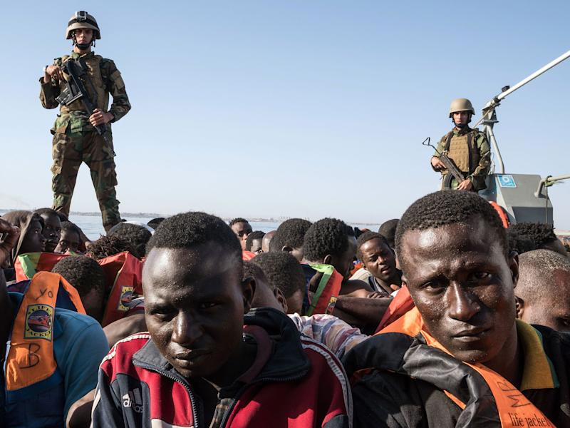 Members of the Libyan coastguard stand on a boat while detaining 147 migrants attempting to reach Europe off the coastal town of Zawiyah on 27 June 2017: Getty
