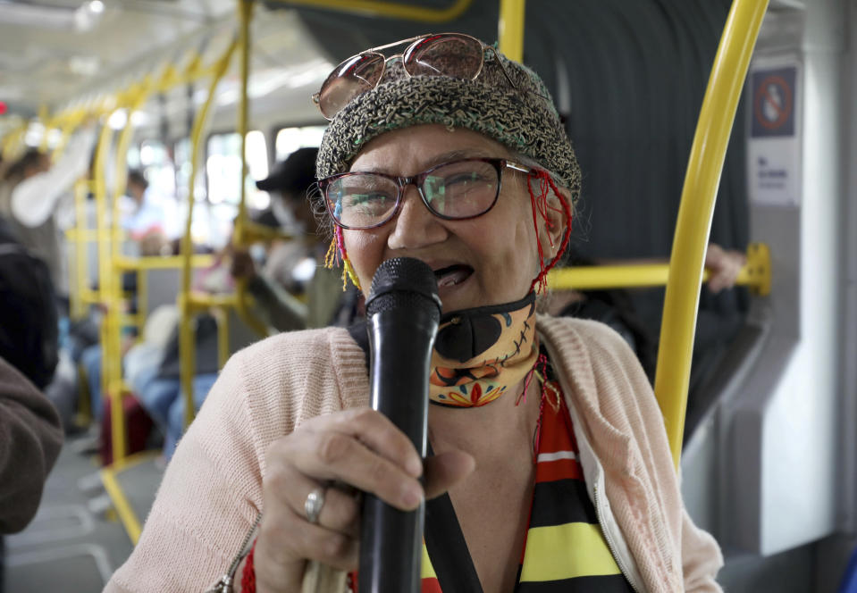 """Marlene Alfonso, a 69-year-old Venezuelan grandmother who goes by """"Toothless Cindy,"""" sings about Venezuelan migrants' lives in hopes of tips from commuters on the Transmilenio, the crowded and crime-ridden public bus system in Bogota, Colombia, Tuesday, Nov. 3, 2020. """"I'm showing people how to not feel defeated,"""" Alfonso said after finishing a set of songs. (AP Photo/Fernando Vergara)"""