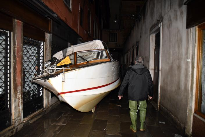 A man looks at a stranded taxi boat lying on its side in a alley in Venice, early Wednesday, Nov. 13, 2019. The mayor of Venice is blaming climate change for flooding in the historic canal city that has reached the second-highest levels ever recorded, as another exceptional water level was recorded Wednesday. The high-water mark hit 187 centimeters (74 inches) late Tuesday, meaning more than 85% of the city was flooded. (AP Photo/Luigi Costantini)