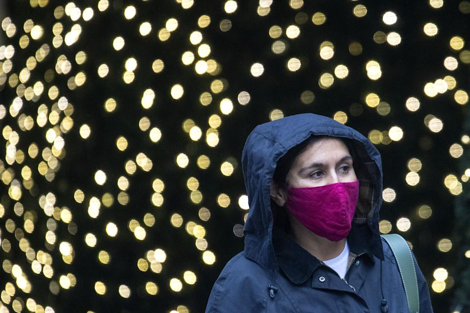 A woman wearing a face mask walks past Christmas lights outside a department store in central London. A new three-tier system of alert levels for England has been implemented following rising coronavirus cases and hospital admissions. (Photo by Dominic Lipinski/PA Images via Getty Images)