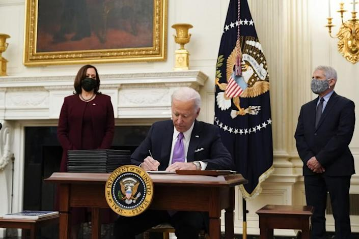 President Joe Biden signs executive orders after speaking about the coronavirus, accompanied by Vice President Kamala Harris, left, and Dr. Anthony Fauci, director of the National Institute of Allergy and Infectious Diseases, right, in the State Dinning Room of the White House, Thursday, Jan. 21, 2021, in Washington. (AP Photo/Alex Brandon)