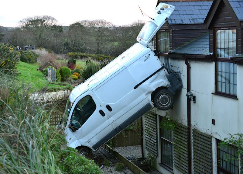 "A white van man is lucky to be alive after he crashed his motor, flipping it and landing it vertically against a hotel near Newquay, Cornwall. Luckily no one was hurt. Simon Hill, owner of the White House Inn said: ""It could have been very dangerous if there had been someone in that room. They would certainly have got a shock."" (SWNS)"