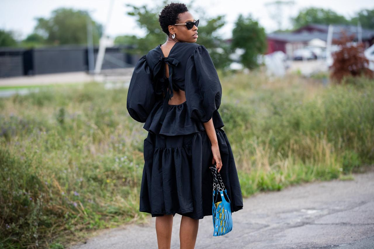 <p>Choose a black puff-sleeve dress with an open back to show some skin.</p>
