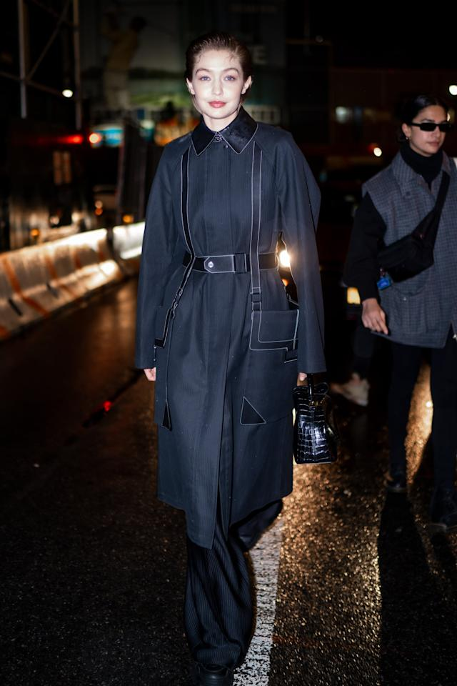 <p>Gigi left the Proenza Schouler show in a tailored trench coat and sneakers, toting a black croc-effect bag.</p>