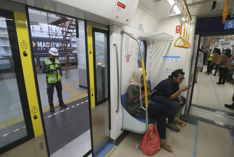 In this Feb. 21, 2019, photo, people ride on a Mass Rapid Transit (MRT) during a trial run in Jakarta, Indonesia. Commuting in the gridlocked Indonesian capital will for some involve less frustration, sweat and fumes when its first subway line opens later this month. The 10-mile system running south from Jakarta's downtown is the first phase of a development that if fully realized will plant a cross-shaped network of stations in the teeming city of 30 million people. (AP Photo/Achmad Ibrahim)