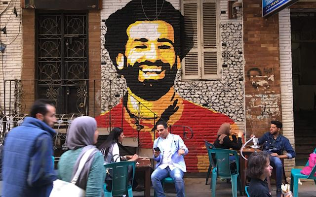 """Every time Mohamed Salah scores, a roar booms around the streets and a city is consumed by unrestrained appreciation. This is not Anfield. This is not Liverpool. This is match day in Cairo, and it is a scene replicated across Egypt at least 41 times this season. In Bain El Sarayat in Giza, a predominantly student area of Egypt's capital, murals of Salah adorn the walls. The students congregate at cafes, such as Bondouk, a short distance from Cairo University, anticipating Salah's weekly goal dispatch. YouTube channels set up by Egyptian fans dedicated to the Liverpool forward are instantly updated. Social media trending is determined by his latest exceptional deed. """"Salah is a role model for young people. The good thing about him is that he started from the bottom and worked hard to succeed,"""" says Islam Helmy, 20. """"He comes from a village, and I'm from a village, too. I love him so much. I made my haircut and my beard just like him. """"One of the happiest moments in my life was when he scored the penalty in Congo [which qualified Egypt to the World Cup]. I was sitting in the stadium right behind the goal. It was hysterical cheering."""" To the Egyptian people, Salah is more than a talented footballer. He is symbol of hope for a generation healing the scars of social change, and the nature of his journey matters as much as his success. Salah emerged during a turbulent period in Egypt, honing his talent while young protesters took to the streets to force the overthrow of President Mubarak in January 2011. """"The Egyptian people look up to Salah as the model of success they can't achieve in their country,"""" says Mohamed Mokhtar, 34, a sales manager. """"We have gone through a hard time after the revolution. There was a feeling of defeat. Salah proved to the people that you could succeed despite the hardships. Nobody has reached this success before."""" Salah is outscoring Messi and is on course to re-write the Premier League record books Mahmoud Gaber, 31, adds: """"The people felt tha"""