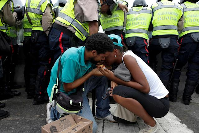 <p>Opposition supporters recover from tear gas next to riot police, in Caracas, Venezuela, June 7, 2016. (Reuters/Carlos Garcia Rawlins) </p>