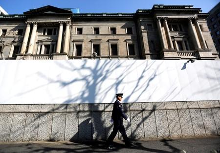 A security guard walks past in front of the Bank of Japan headquarters in Tokyo