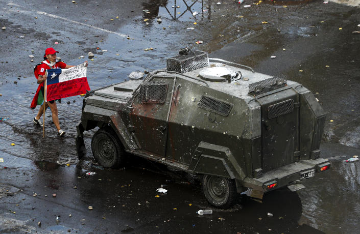 A demonstrator holds a Chilean flag toward an armored police vehicle during an anti-government march in Santiago, Chile, Tuesday, Oct. 22, 2019. (AP Photo/Esteban Felix)