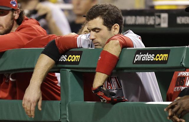 Cincinnati Reds' Joey Votto lens over the rail in the dugout as his team is losing to the Pittsburgh Pirates in the ninth inning of the NL wild-card playoff baseball game on Tuesday, Oct. 1, 2013, in Pittsburgh. The Pirates won 6-2 and advance to the National League Division Series.(AP Photo/Gene J. Puskar)