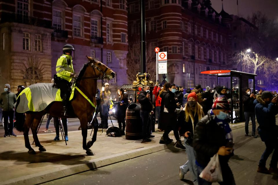 A mounted police officer tries to disperse people on The Victoria Embankment as groups of revellers gather in a near-deserted London late on New Year's Eve, December 31, 2020, as authorities in the Tier 4 city hope the message to stay at home is obeyed. (Photo by Tolga Akmen / AFP) (Photo by TOLGA AKMEN/AFP via Getty Images)